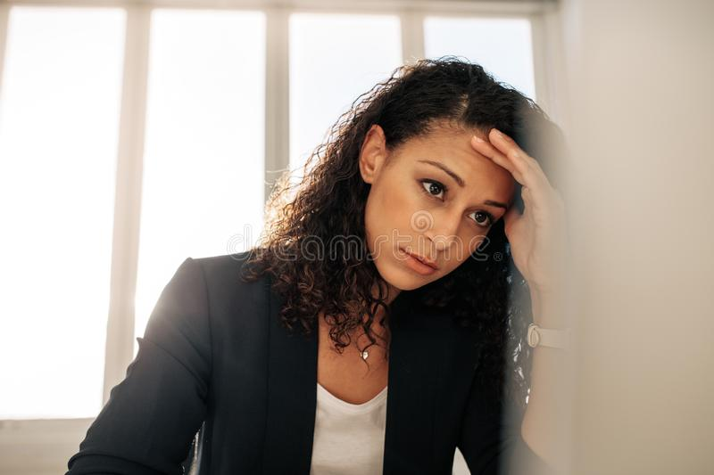 Woman entrepreneur sitting in office holding her head royalty free stock photos