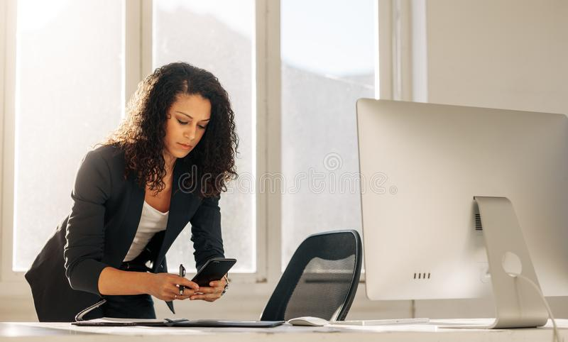 Woman entrepreneur using cell phone standing at her desk royalty free stock photography
