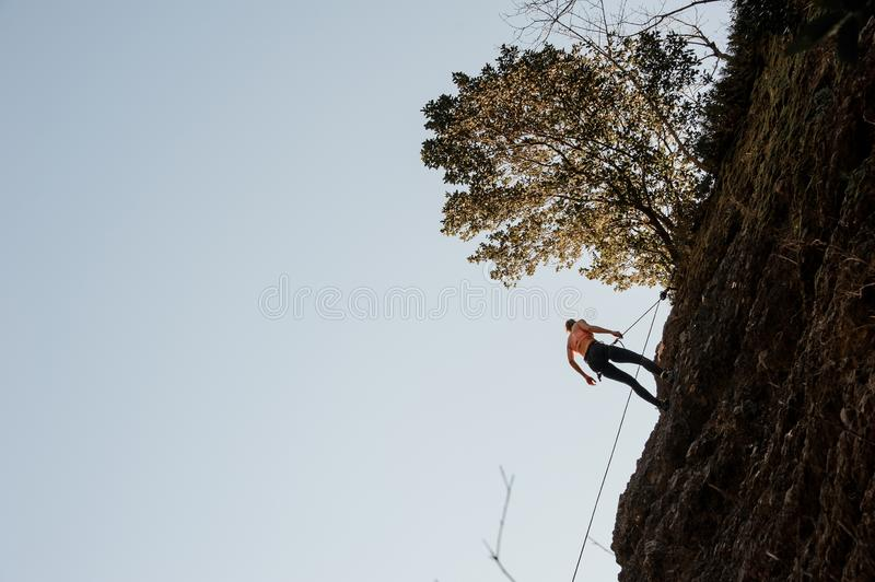 Woman equipped with a rope abseiling on the sloping rock royalty free stock photos