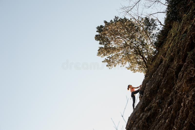 Woman equipped with a rope climbing on the sloping rock royalty free stock photography