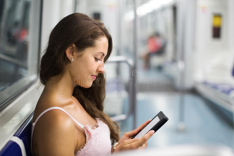 Woman with ereader in subway train. Woman using ereader in subway train at metro royalty free stock images