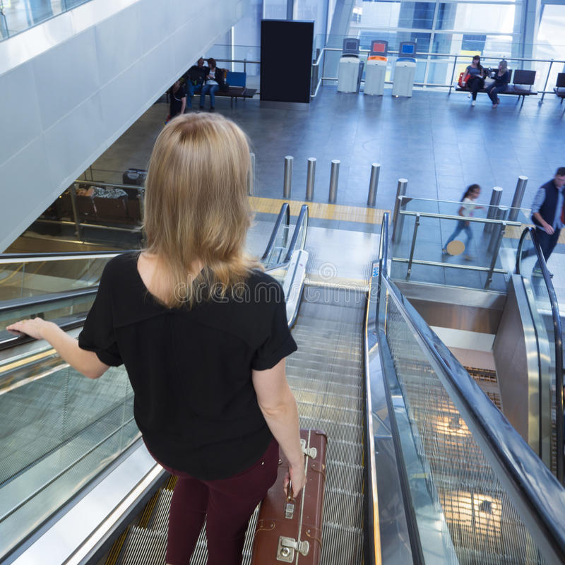 Woman on the escalator in the airport lobby. Lady with a vintage royalty free stock photos