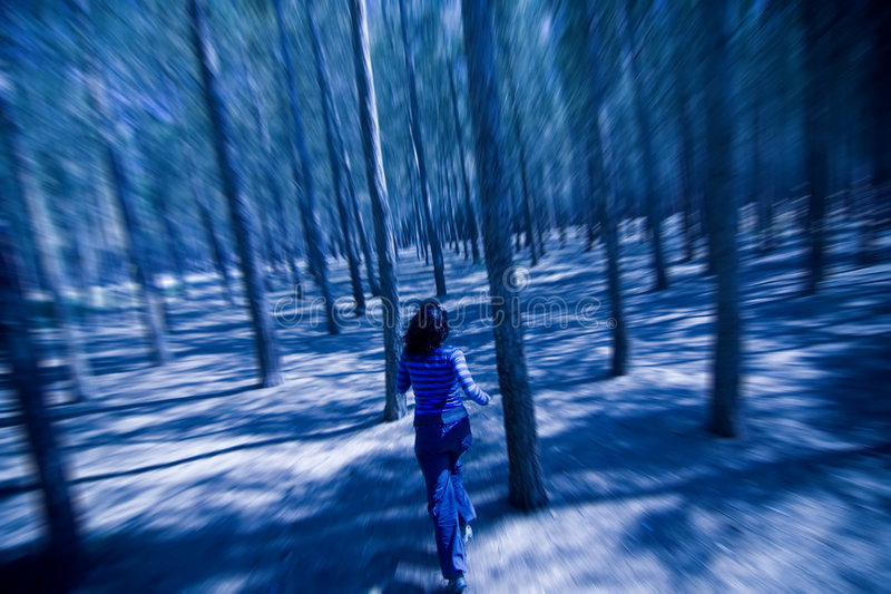 Woman escaping through the woods stock images