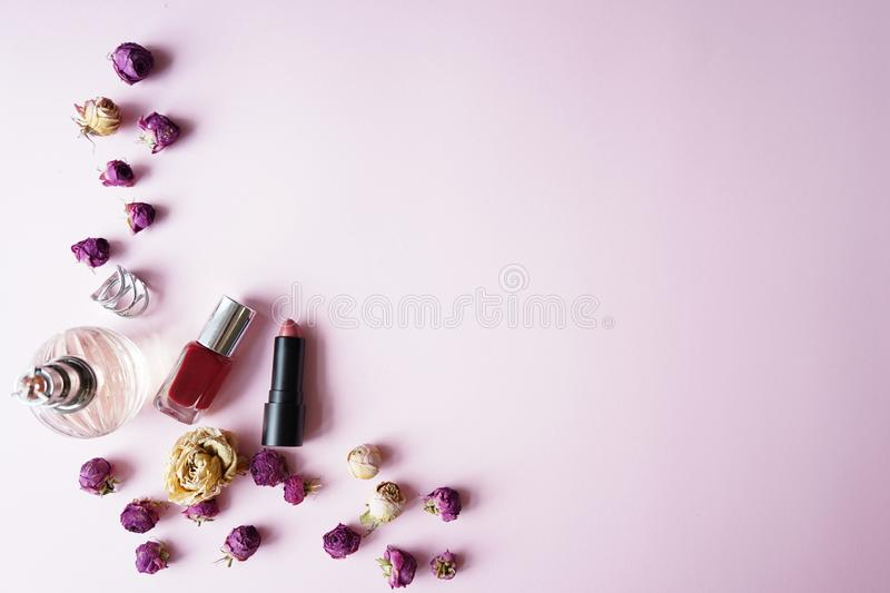 Woman essential accessory Flat lay . on pink pastel background .Top view copy space, lipstick, perfume , roses stock photo