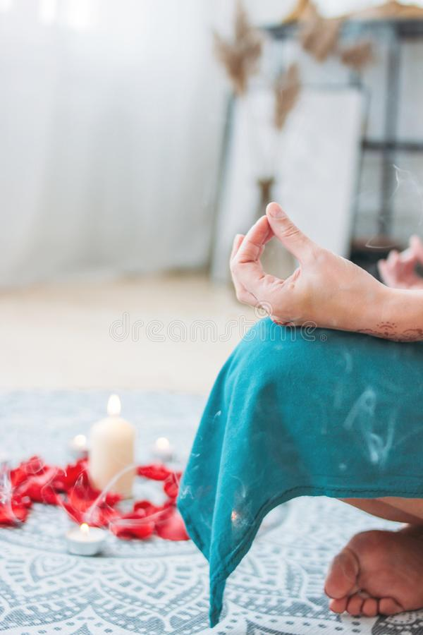 Woman in ethnic costume practicing yoga in front of candles and red rose petals, hands with mehendi stock photos