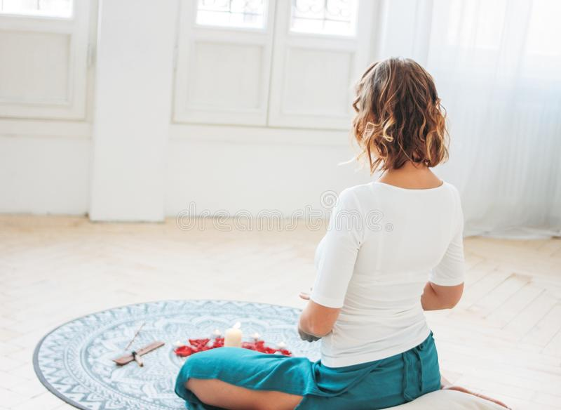 Woman in ethnic costume practicing yoga in front of candles and red rose petals, view from back stock photos