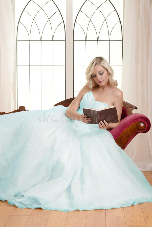 Woman in evening dress sitting on couch reading book stock photography