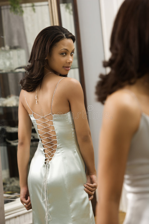Woman in evening gown. Attractive African-American woman wearing evening gown looking in mirror stock photos