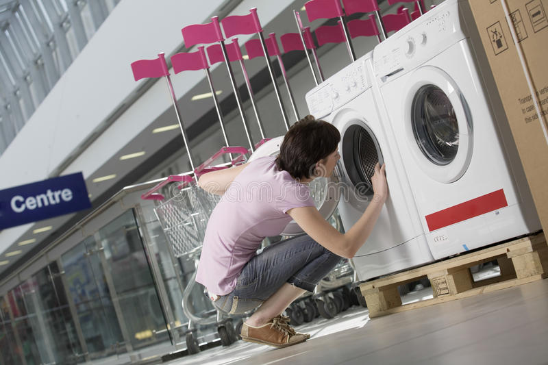 Download Woman Examining Front Loader Of Washing Machine Stock Image - Image of consumerism, mall: 33900809