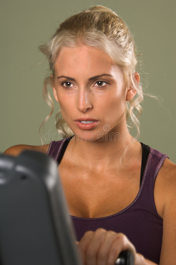 Woman on Exercise Bike royalty free stock photography