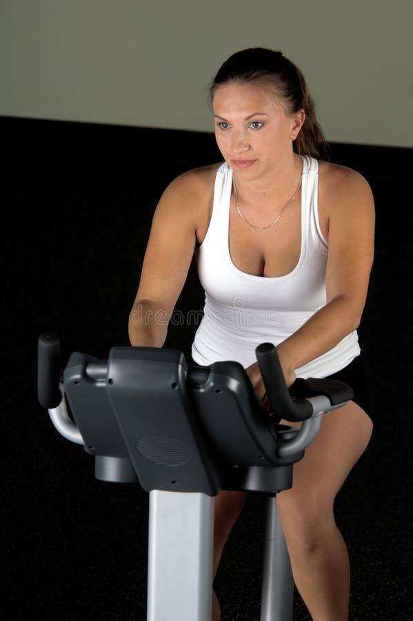 Woman on Exercise Bike royalty free stock image
