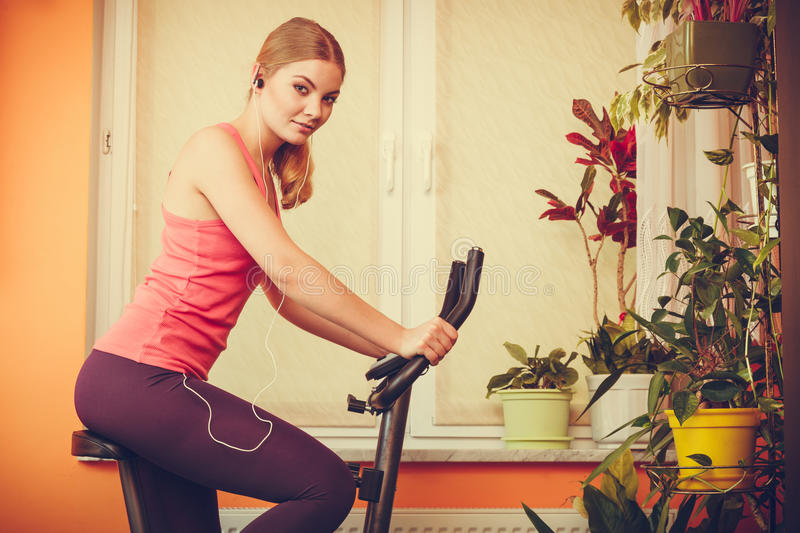 Woman on exercise bike listening music. Fitness stock images
