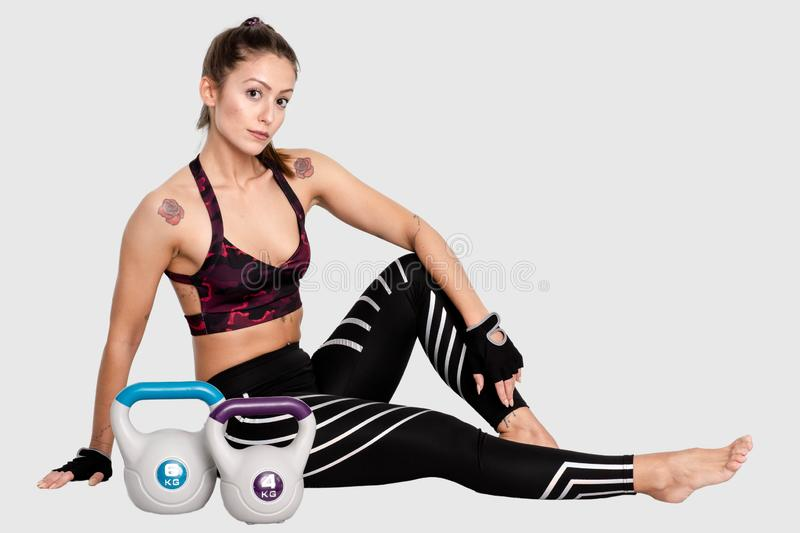 Woman exercise, fitness breaking relax after kettlebell workout or sitting tired,rest training sport healthy lifestyle. Image. Woman exercise, fitness breaking stock image