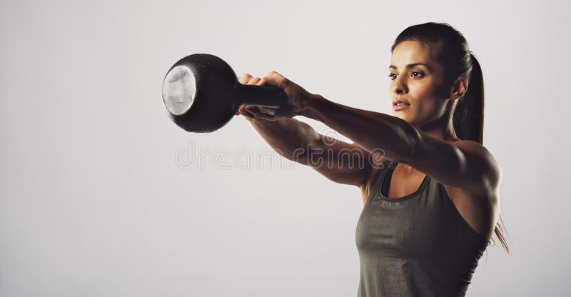 Woman exercise with kettle bell - Crossfit workout. Young fitness female exercise with kettle bell. Mixed race woman doing crossfit workout on grey background royalty free stock photography