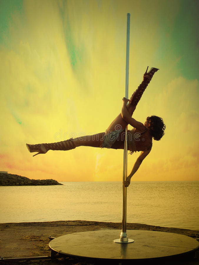 Woman exercise pole dance against sunset sea landscape. Young woman exercise pole dance against sunset sea landscape royalty free stock image
