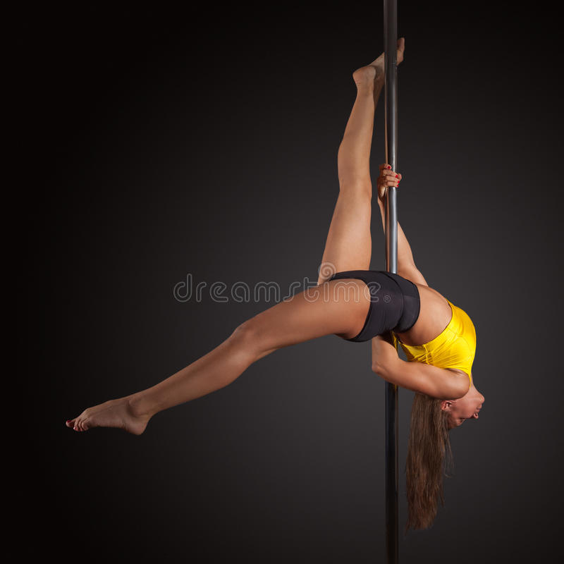 Woman exercise pole dance on gray background. Young woman exercise pole dance before a gray background stock photography