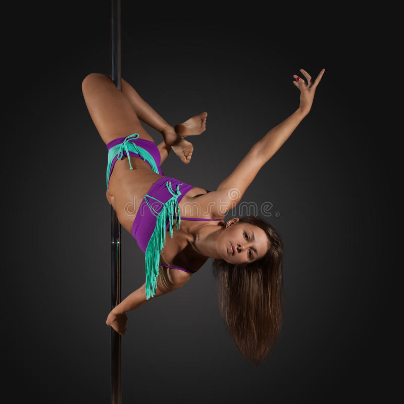 Woman exercise pole dance on gray background. Young woman exercise pole dance before a gray background stock image