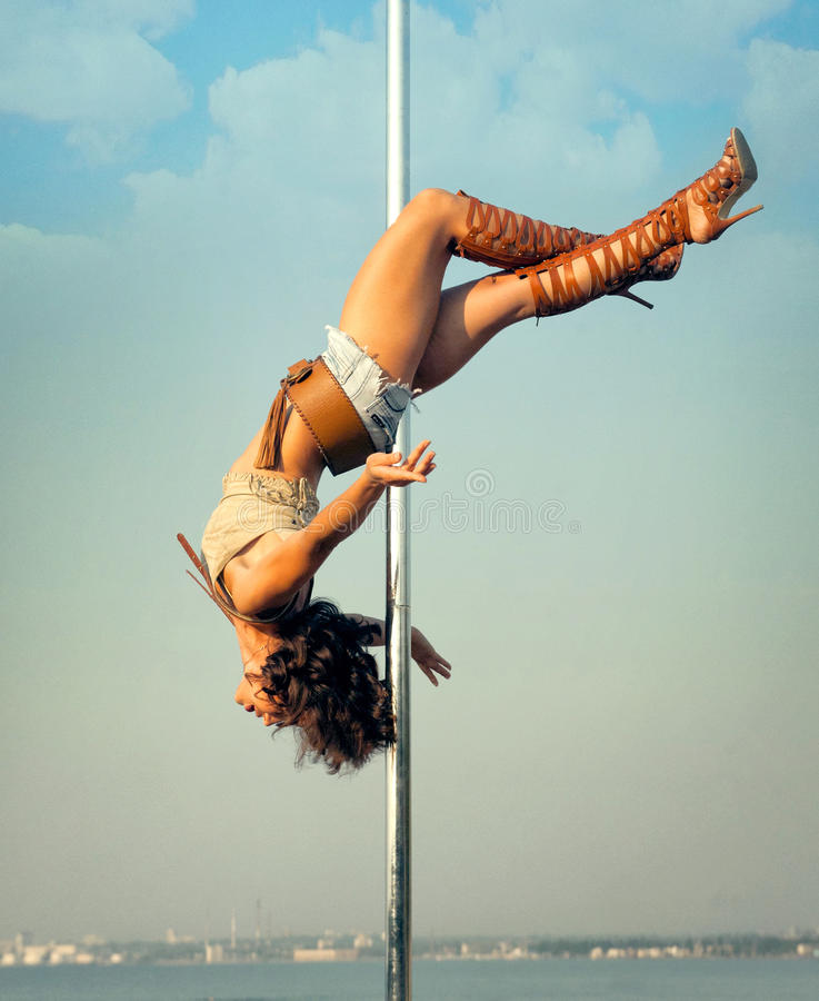 Woman exercise pole dance outdoors. Young woman exercise pole dance outdoors royalty free stock photos