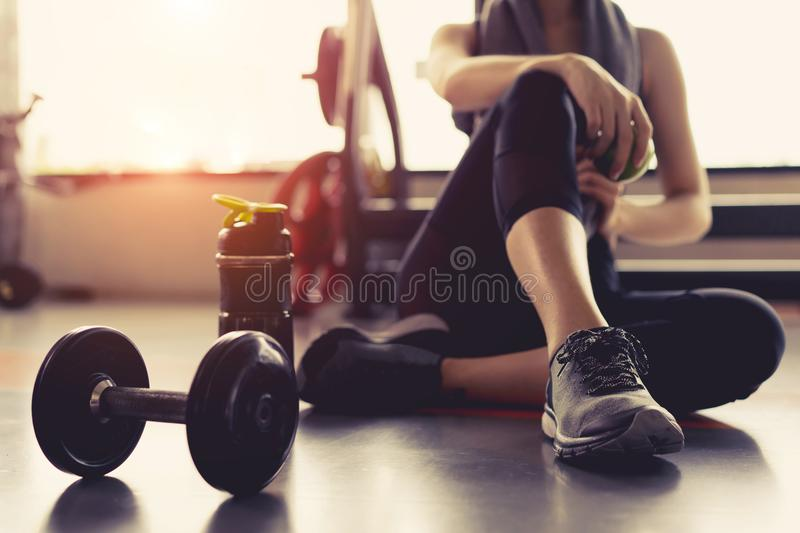 Woman exercise workout in gym fitness breaking relax holding apple fruit after training sport royalty free stock photo