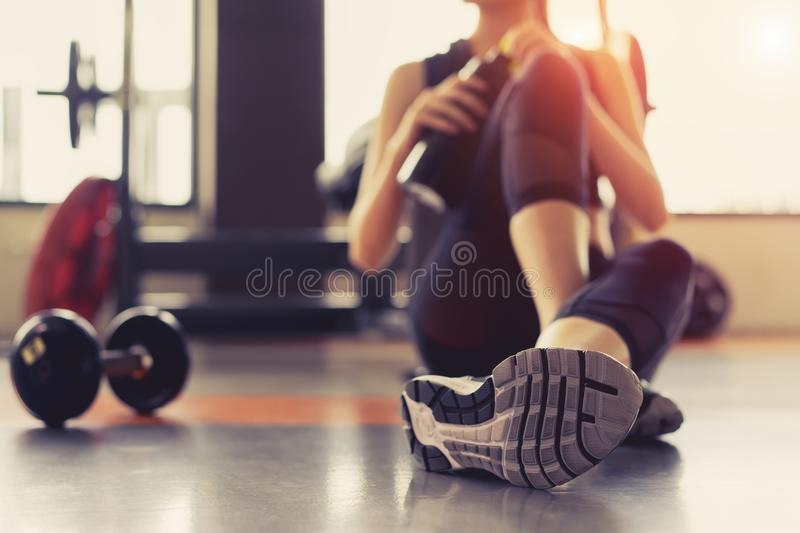 Woman exercise workout in gym fitness breaking relax holding protein shake. Bottle after training sport with dumbbell and healthy lifestyle bodybuilding stock photo
