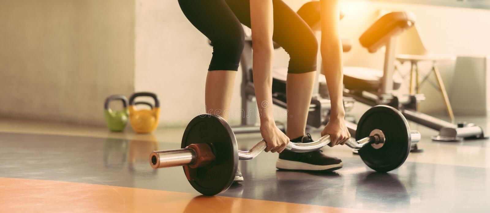 Woman exercise workout at gym fitness training sport with barbell weight stock photos
