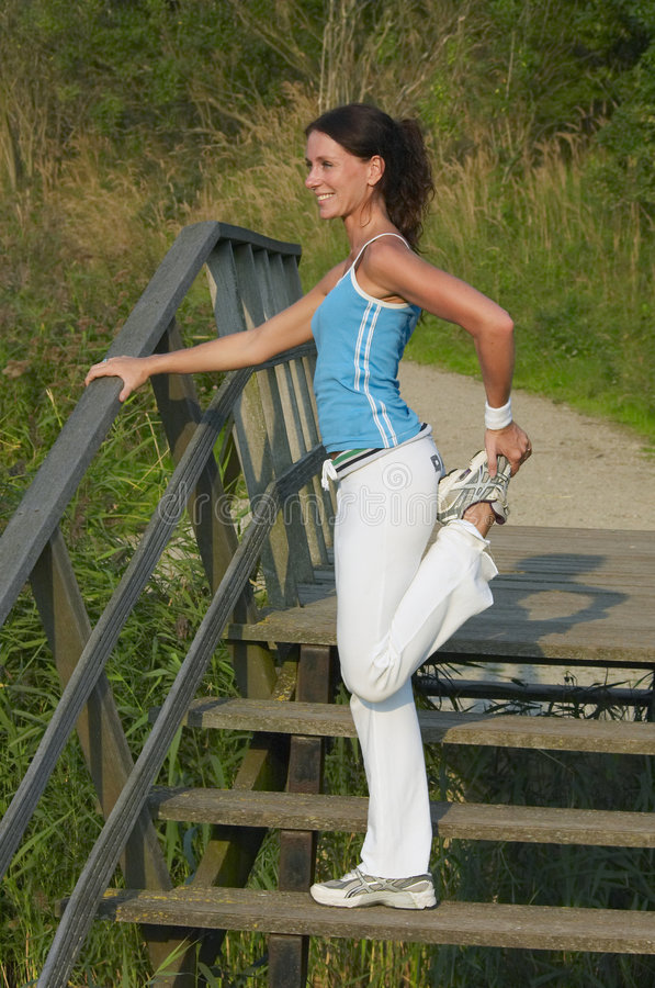 Woman exercising. Young healthy woman exercising outdoor royalty free stock image