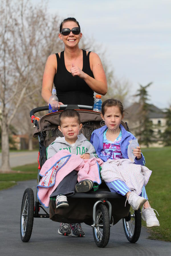 Woman exercising. A woman with a stroller exercising with kids stock photos