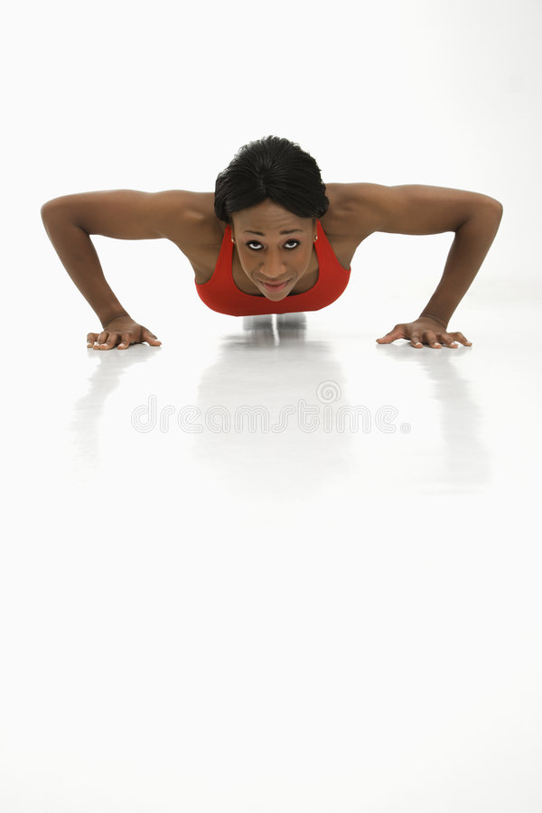 Woman exercising. African American young adult woman doing push up and looking at viewer stock photos