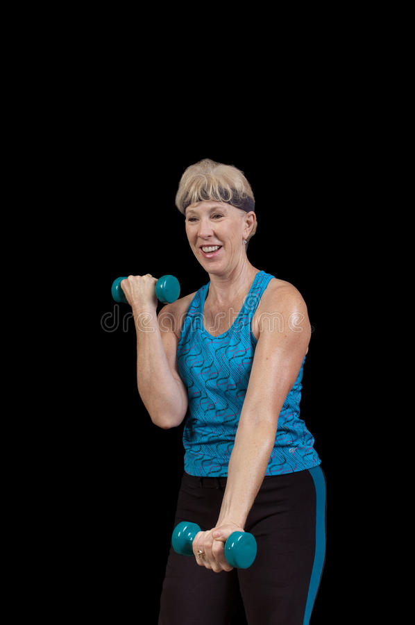 Woman exercising. Attractive baby-boomer exercising with weights isolated over black stock photography
