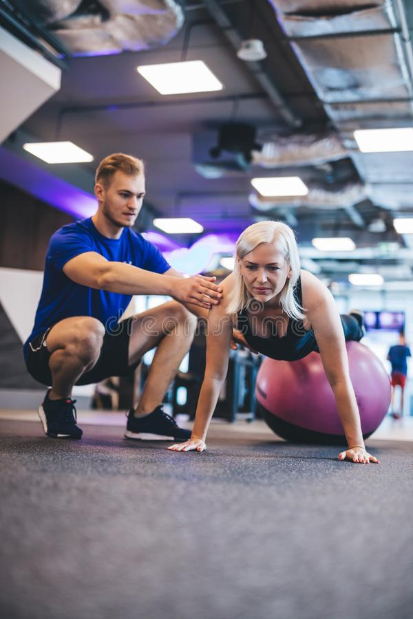 Woman exercising on a ball and a man securing her. stock image