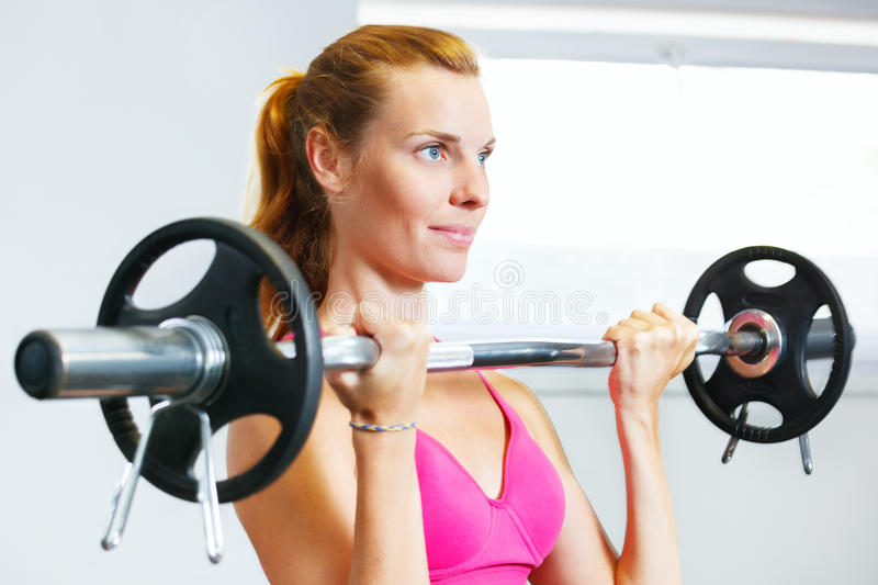 Woman exercising with barbell. Young woman exercising with barbell in gym stock photography