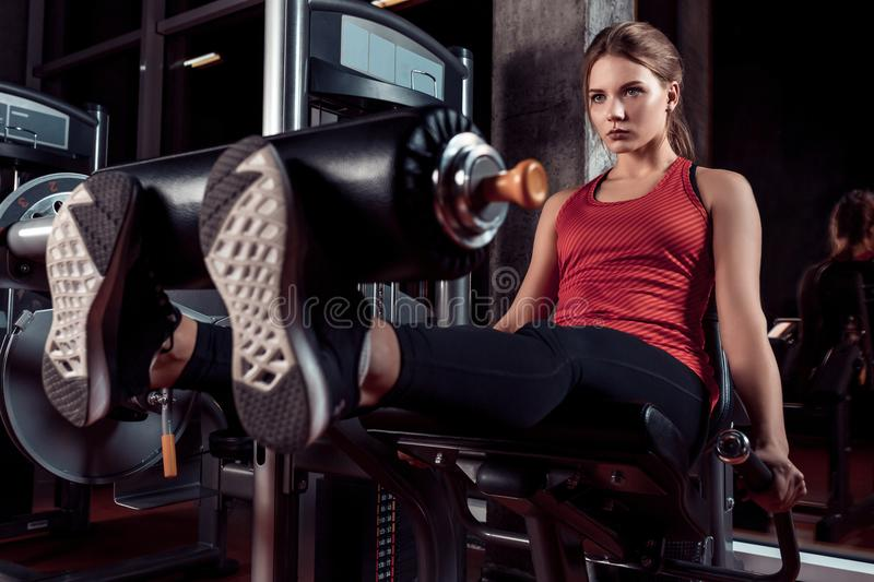 Woman exercising with crossover in fitness club or gym training legs. On a dark background the gym. Dressed in sport clothes stock images