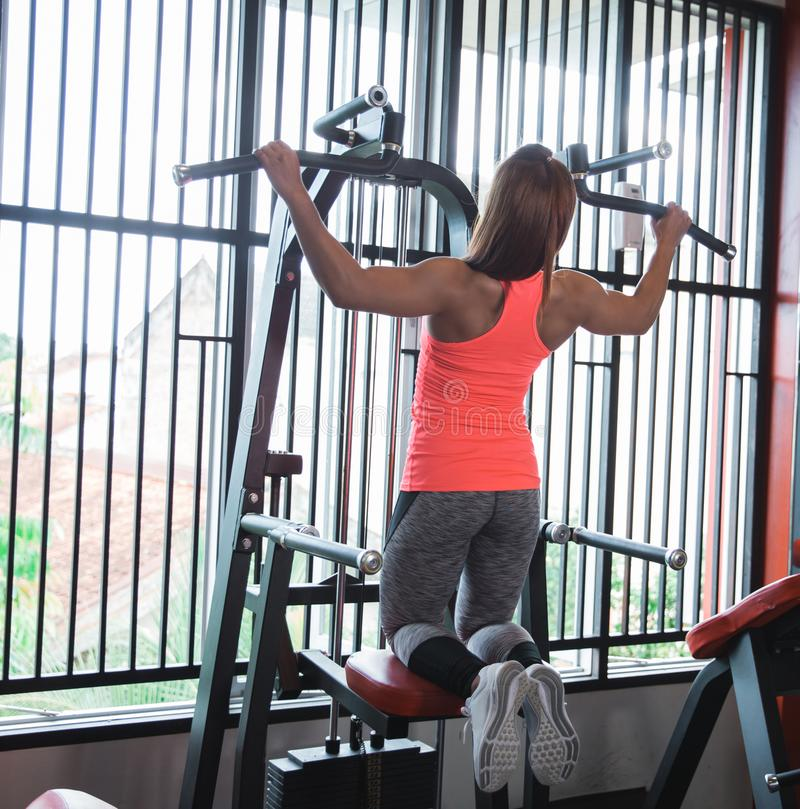 Woman exercising and doing pull ups stock images