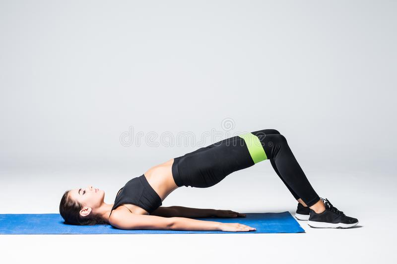 Woman exercising doing workout for legs with elastic bands lying on floor isolated on white background royalty free stock images