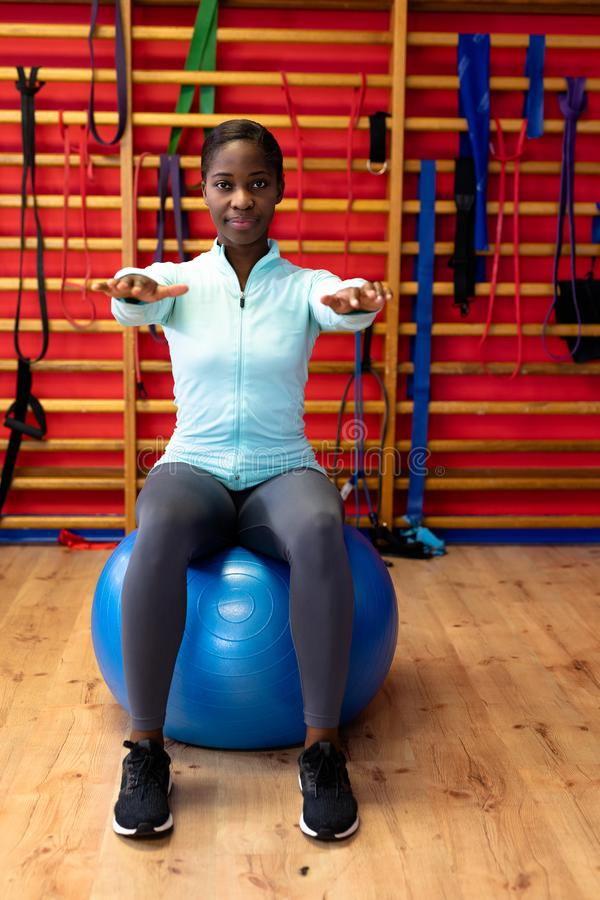Woman exercising with exercise ball in sports center. Front view of woman exercising with exercise ball in sports center. Sports Rehab Centre with royalty free stock photos