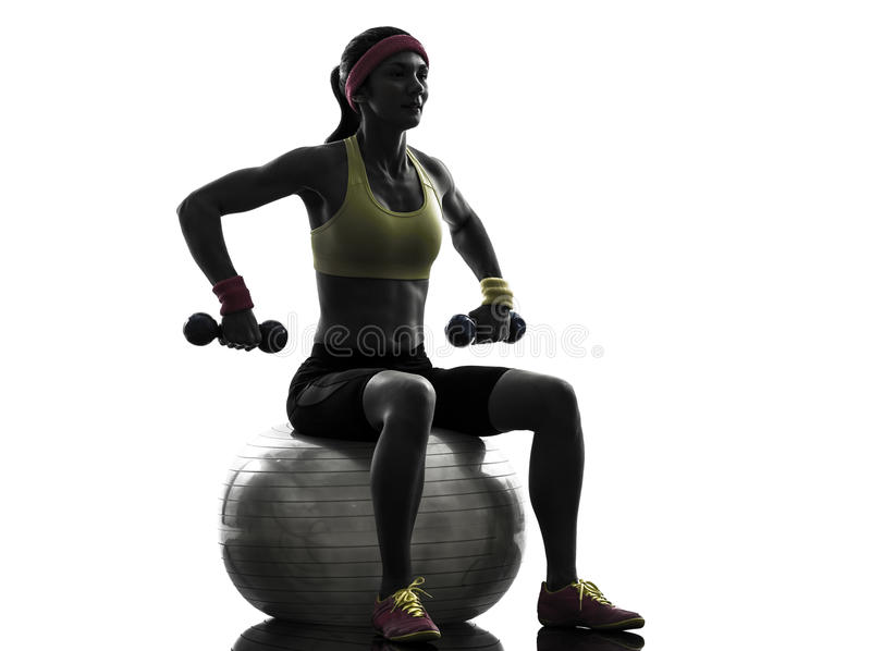 Woman exercising fitness ball weight training silhouette stock photography