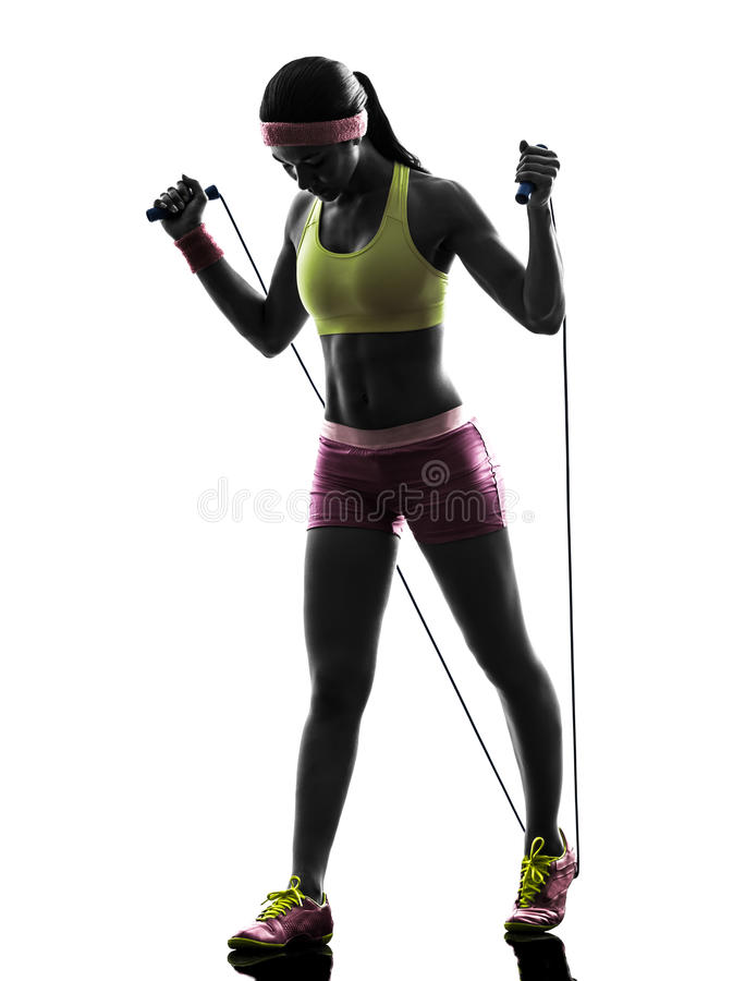 Woman exercising fitness jumping rope silhouette. One caucasian woman exercising fitness jumping rope in silhouette on white background royalty free stock photo
