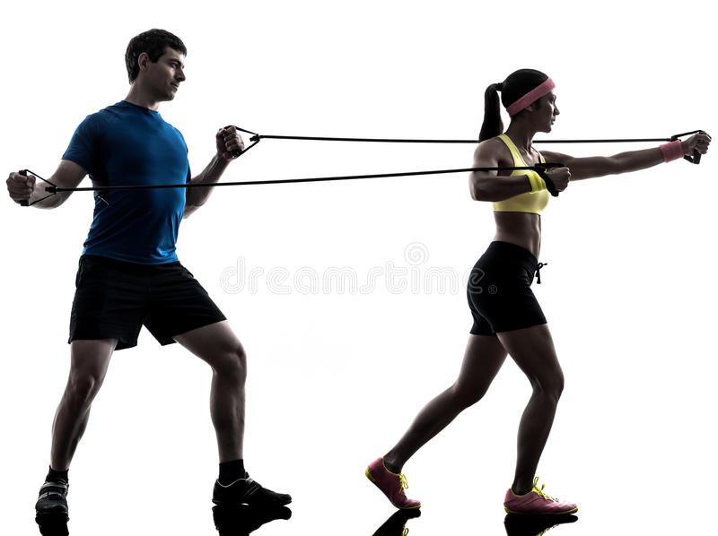 Woman exercising fitness resistance rubber band with man coach royalty free stock photos