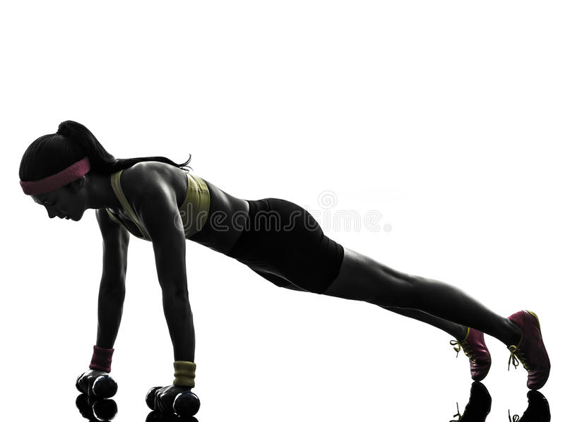 Woman exercising fitness workout push ups silhouette. One woman exercising fitness workout push ups in silhouette on white background royalty free stock images