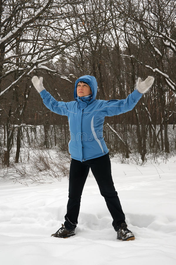 Woman exercising in the fresh air. In the winter forest stock image