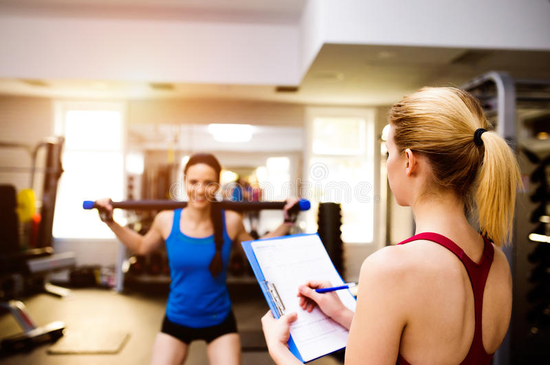 Woman exercising in gym, personal trainer, plan on clipboard stock photos
