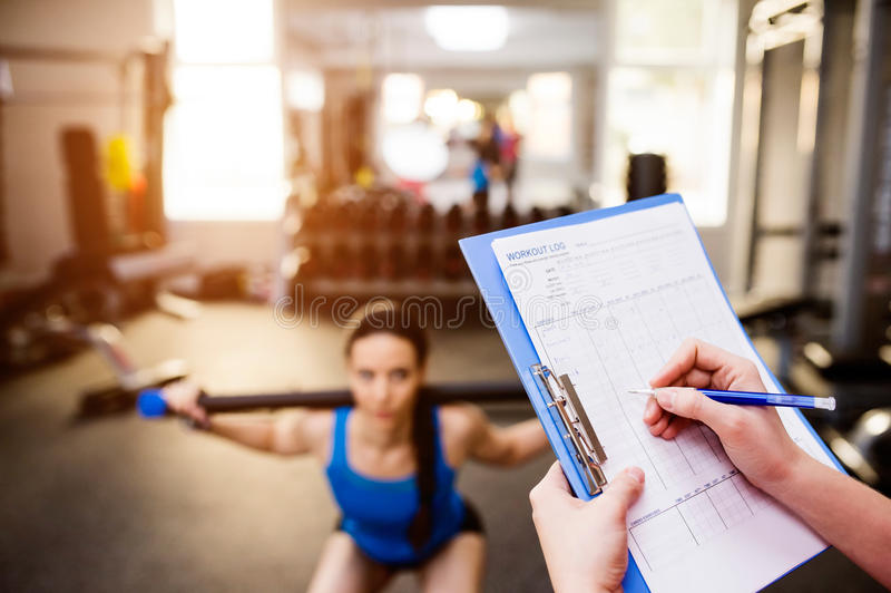 Woman exercising in gym, personal trainer, plan on clipboard royalty free stock images