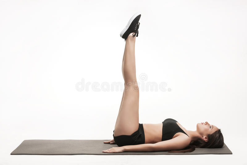 Woman exercising on man. Portrait of young attractive woman doing exercises. Brunette with fit body on yoga mat. Healthy lifestyle and sports concept. Series of royalty free stock photos
