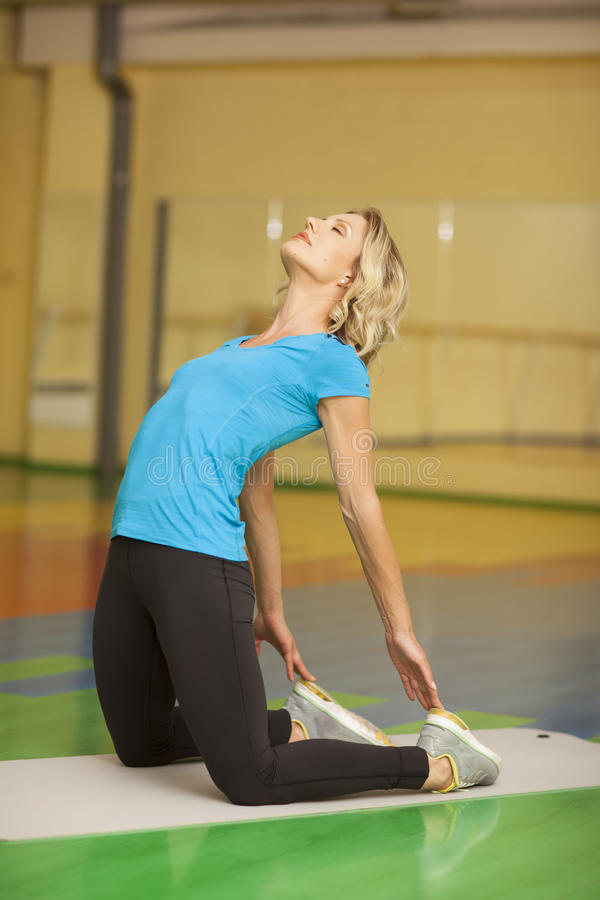 Woman exercising on mat in fitness class. Female stretching after workout looking up stock photo