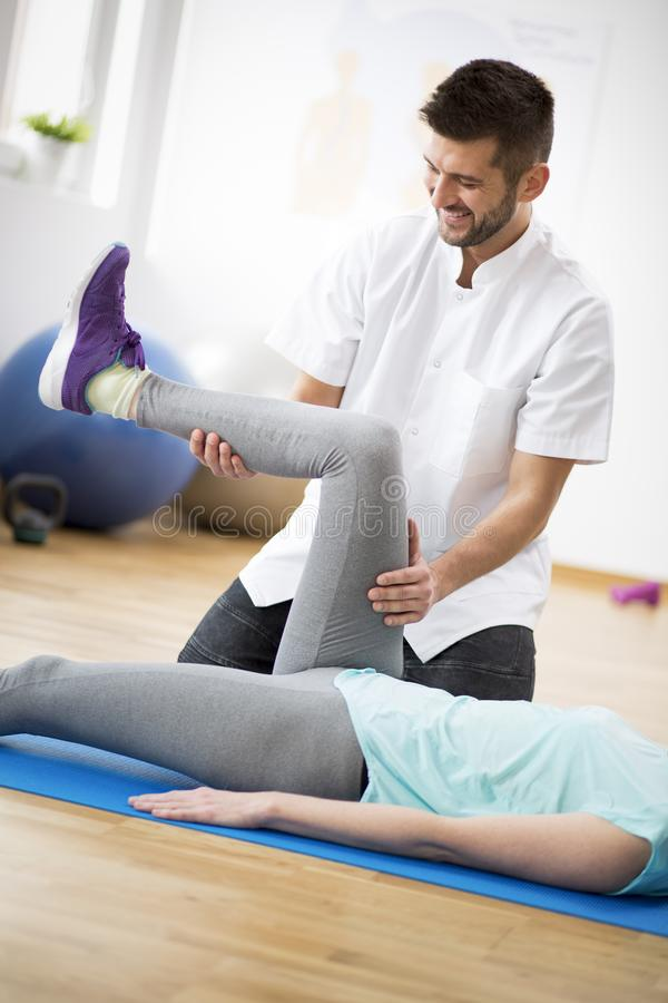 Middle age woman exercising on blue mat during physiotherapy with young male doctor. Woman exercising on mat during physiotherapy with young male doctor royalty free stock photography