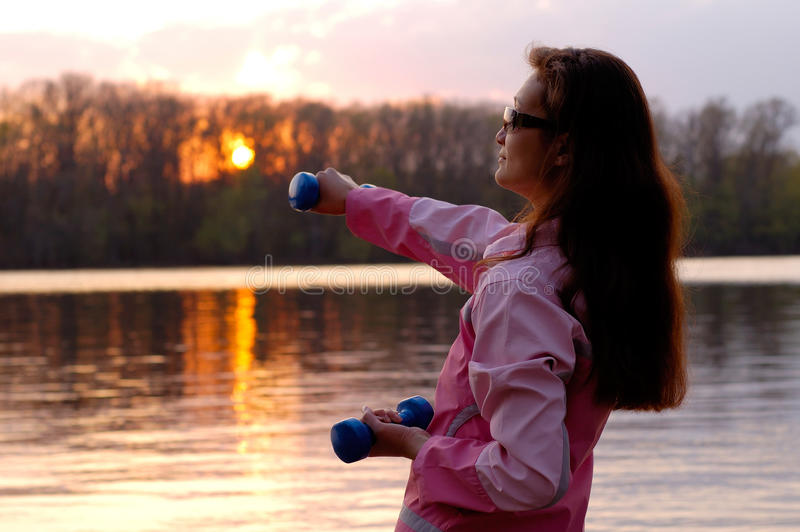 Woman Exercising in the Nature. Young woman with weights exercising in the nature in sunset near the river Healthy lifestyle and fitness concept royalty free stock photo