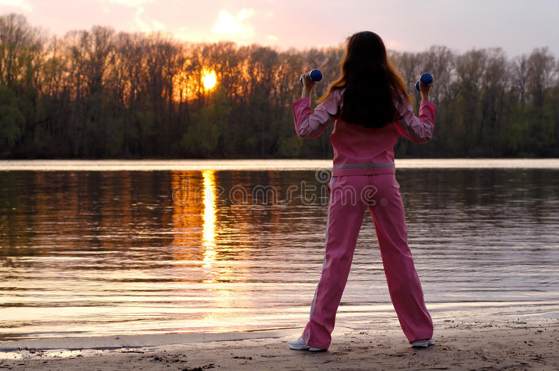 Woman Exercising in the Nature. Young woman with weights exercising in the nature in sunset near the river Healthy lifestyle and fitness concept royalty free stock image