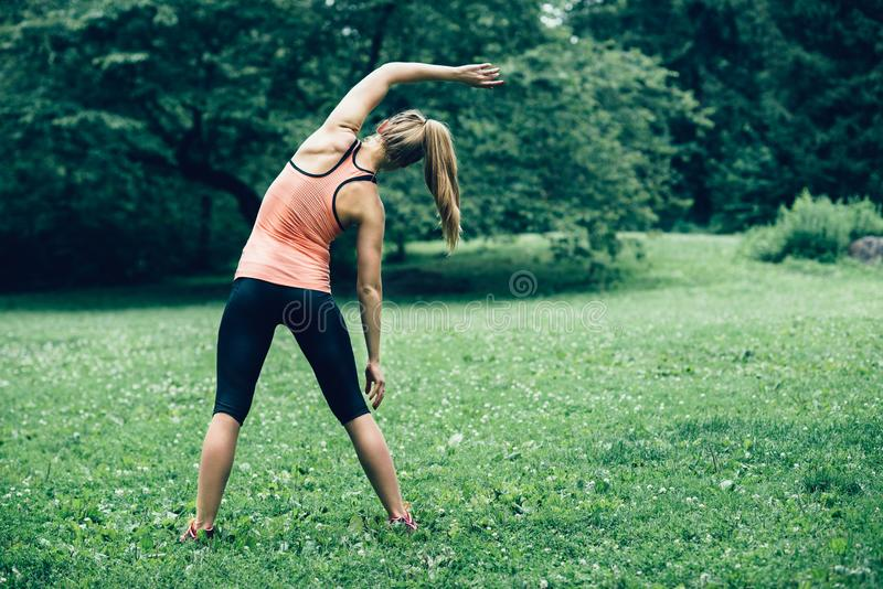 Woman exercising on nature forest lawn at the morning. royalty free stock image