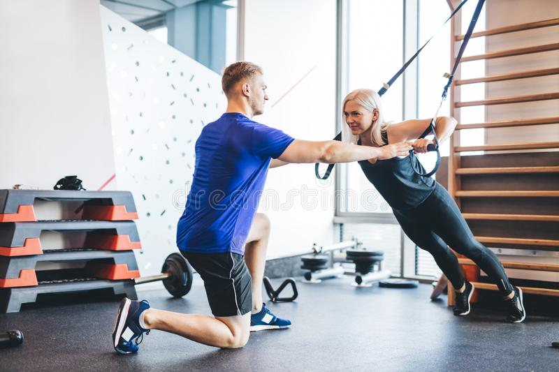 Woman exercising with personal trainer at the gym. stock image