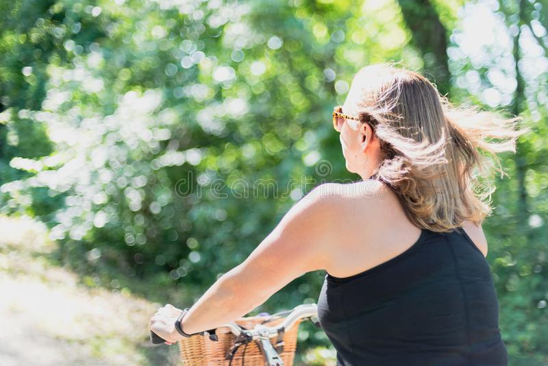 Woman exercising riding bicycle royalty free stock images